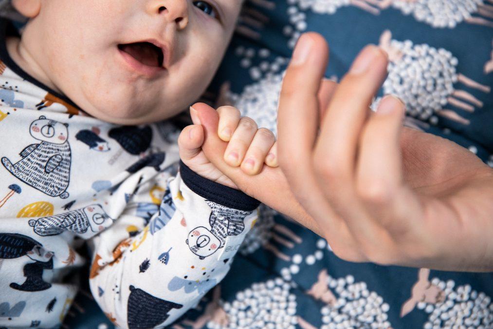 Vauva tarraa aikuisen sormesta