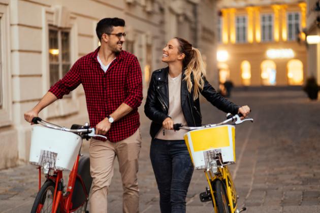 Kuvituskuva, jossa kaksi ihmistä taluttavat pyöriä iloisina